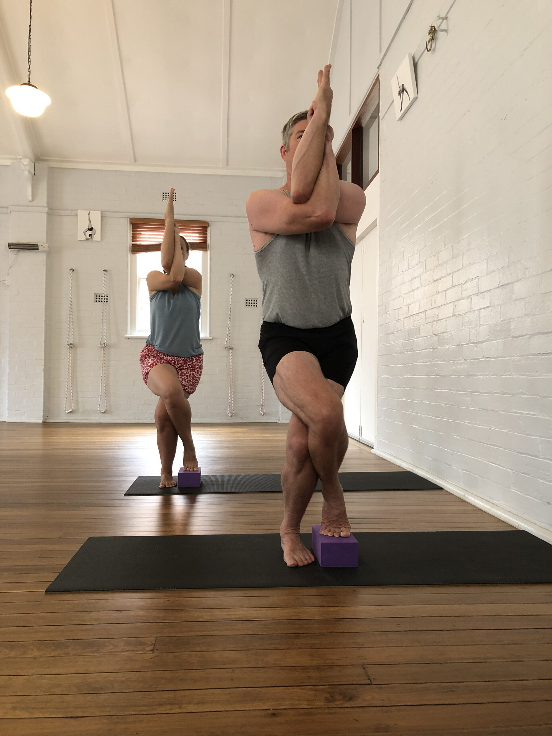 Teachers in Eagle Pose (garudasana) at Hamilton Yoga in Newcastle New South Wales